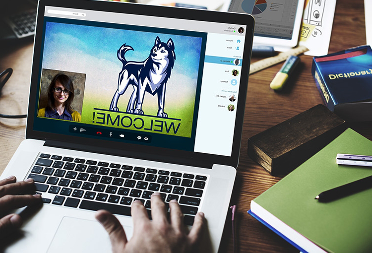 An open laptop displaying an illustration of a Husky standing atop the word 'Welcome' with an inset of a person on a video chat. Two hands are poised over the keyboard and an array of school supplies and study materials surround the laptop.